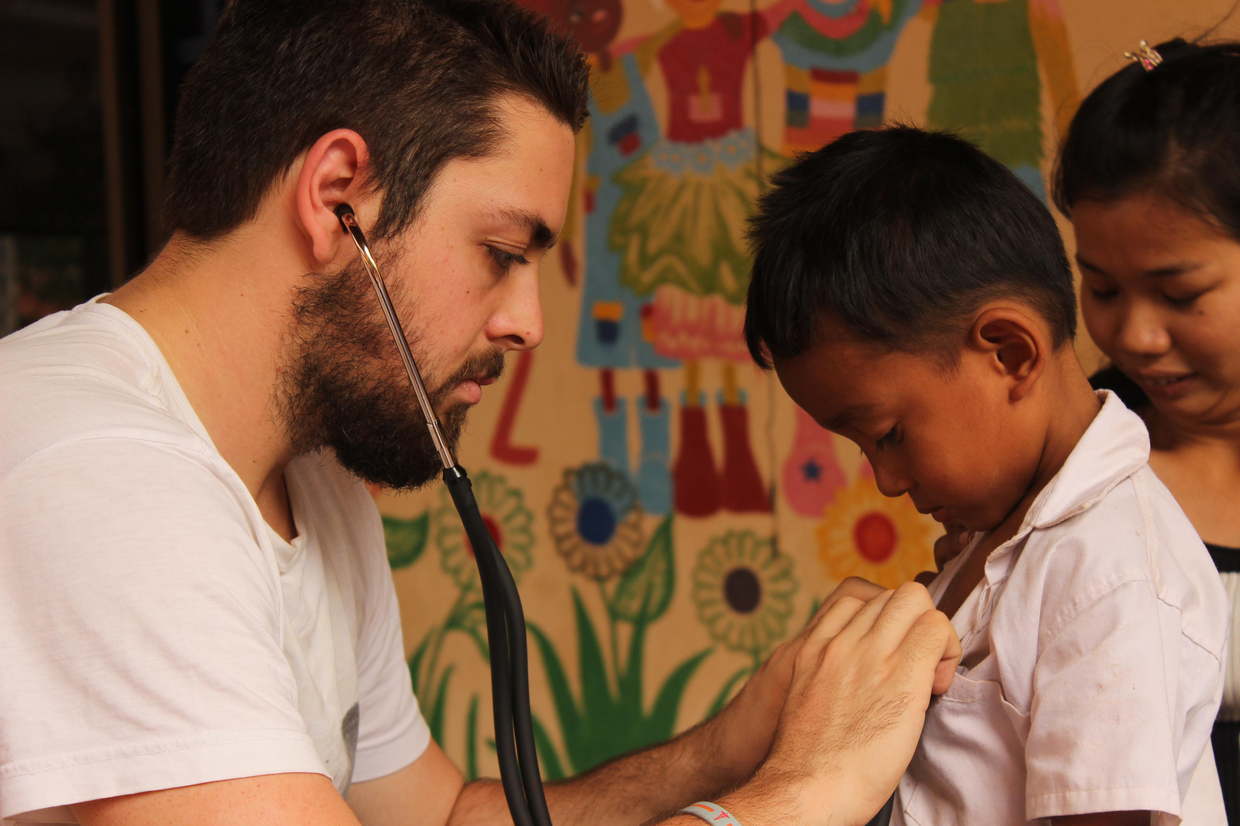Cambodian child is treated by a male medical intern during a local outreach programme.